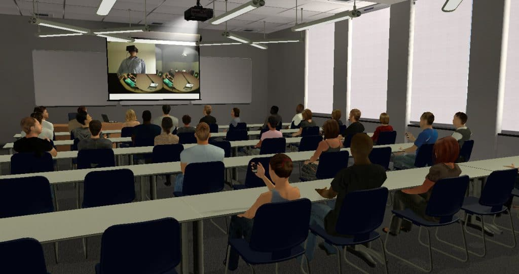 Classroom setup for a slide presentation, seen from the back of the room. The projection is showing an image of someone using an HMD in Virtual Orator taken from the recording mechanism. The audience is mostly attentive, but we see a few at the back using their mobile telephones.