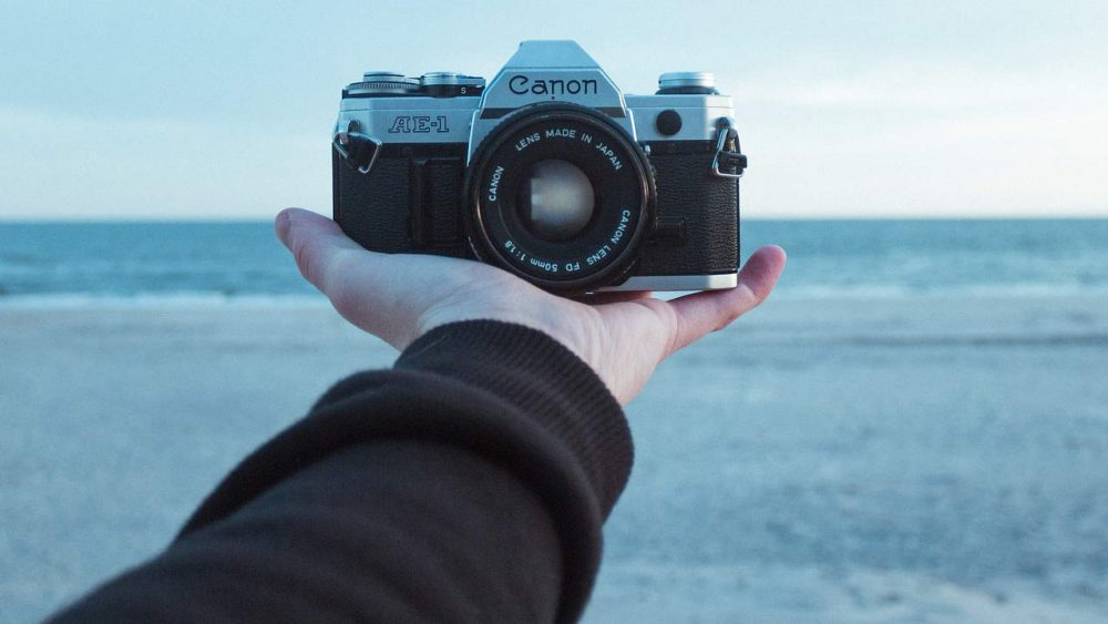 A SLR camera is held in an outstretched hand, but filpped to look back at the photographer.